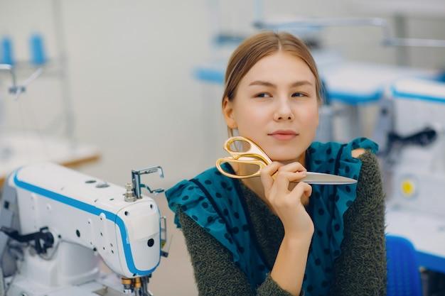 Costurera hermosa joven que sostiene las tijeras en la máquina de coser en fábrica