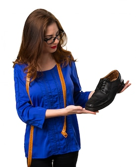 Costurera joven y bonita con cinta métrica y sosteniendo un zapato