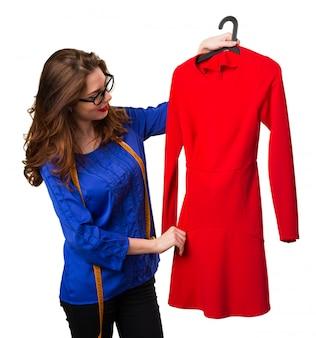 Costurera joven y bonita con cinta métrica y un vestido rojo