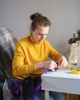 Costurera mujer feliz mirando futura prenda mientras trabaja de forma remota en su espacio de trabajo en casa