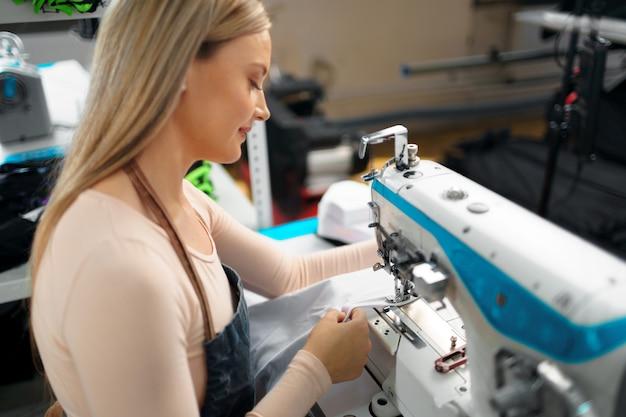 Costurera mujer hermosa trabajando con tela en su lugar de trabajo