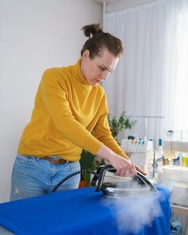 Costurera de mujer planchando tela naranja mientras trabajaba en su lugar de trabajo