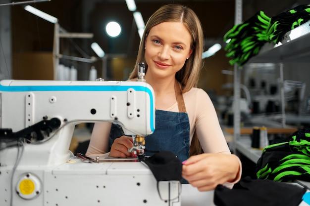 Costurera mujer en su lugar de trabajo cosiendo ropa en la máquina de coser