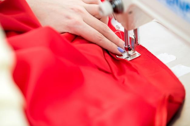 Costurera de niña cose en la máquina de coser