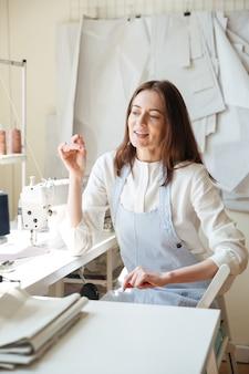 Costurera sentada cerca de la máquina de coser y hablando