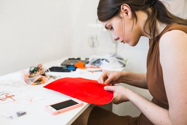 Costurera de sexo femenino joven que cose la tela roja