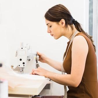 Costurera de sexo femenino que trabaja en la máquina de coser