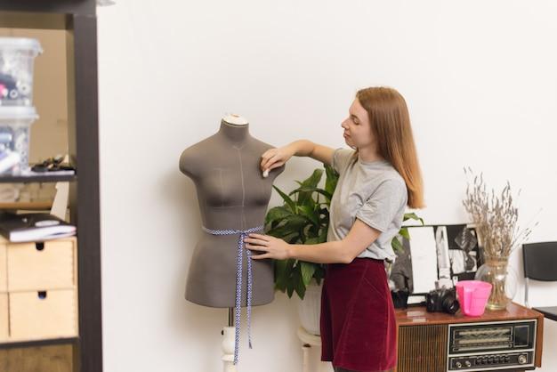 Costurera toma medidas con tiza en un maniquí en la oficina. patrón de mujer inactiva en un taller de costura