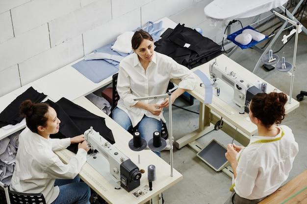 Una de las costureras jóvenes que consulta a sus colegas sobre los detalles de los nuevos modelos de colección de temporada y las tendencias en una reunión en el taller.