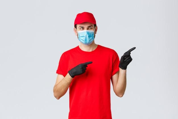 Covid-19, auto-cuarentena, compras en línea y concepto de envío. repartidor sonriente intrigado con camiseta roja, uniforme de portador de gorra, usando máscara médica y guantes para entregar al cliente, apunte a la derecha