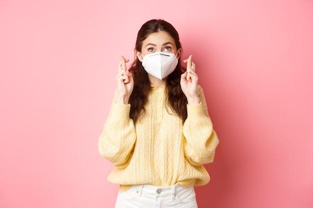 Covid-19, concepto de bloqueo y pandemia. mujer joven luce esperanzada, pide deseos con los dedos cruzados, usa máscara médica, respirador de coronavirus, pared rosa.