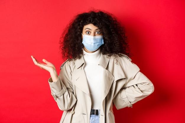 Covid-19, concepto de distanciamiento social y cuarentena. mujer europea sorprendida y confundida con cabello rizado, con máscara médica del coronavirus, levanta la mano desconcertada, pared roja.