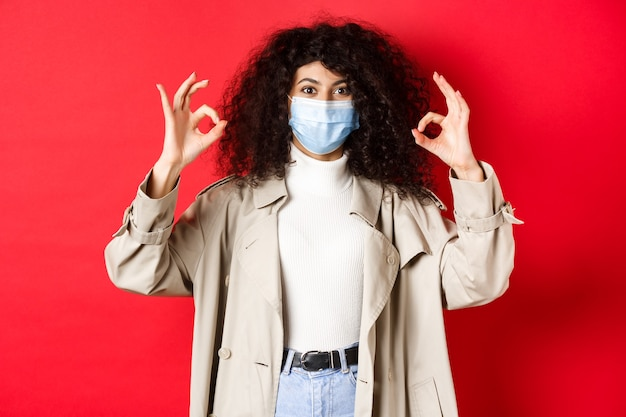 Covid-19, concepto de distanciamiento social y cuarentena. mujer de moda con el pelo rizado, con máscara médica y gabardina, mostrando gestos bien, fondo rojo.