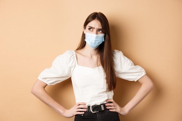 Covid-19 y concepto de estilo de vida. mujer sospechosa en máscara médica con el ceño fruncido, mirando a un lado el logo con rostro dudoso, de pie sobre fondo beige.