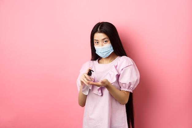Covid-19, concepto de estilo de vida y salud. hermosa mujer asiática en máscara médica limpia las manos con desinfectante, aplica antiséptico en las palmas, de pie sobre fondo rosa.
