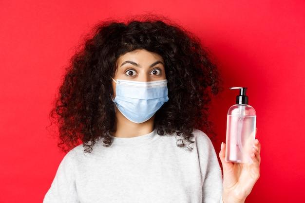 Covid-19, concepto de pandemia y cuarentena. chica emocionada con cabello rizado, con máscara médica, mostrando una botella de desinfectante para manos o antiséptico, de pie sobre la pared roja.