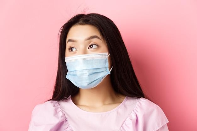Covid-19, concepto de pandemia y cuarentena. primer plano de una soñadora asiática en máscara médica mirando a la izquierda en el logo con rostro pensativo, de pie sobre fondo rosa.