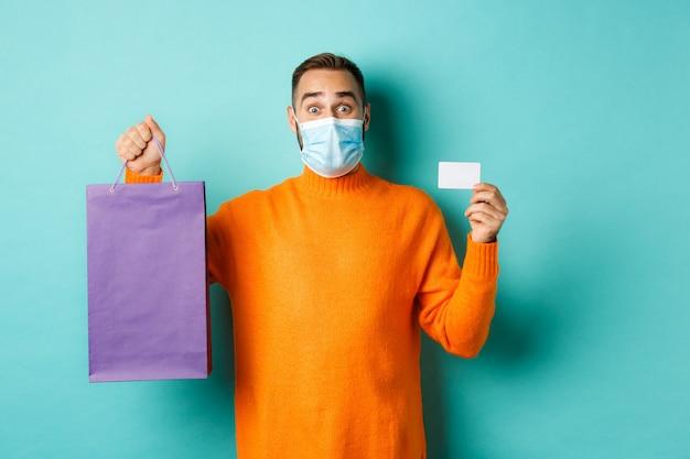Covid-19, concepto de pandemia y estilo de vida. cliente masculino feliz mostrando tarjeta de crédito y púrpura