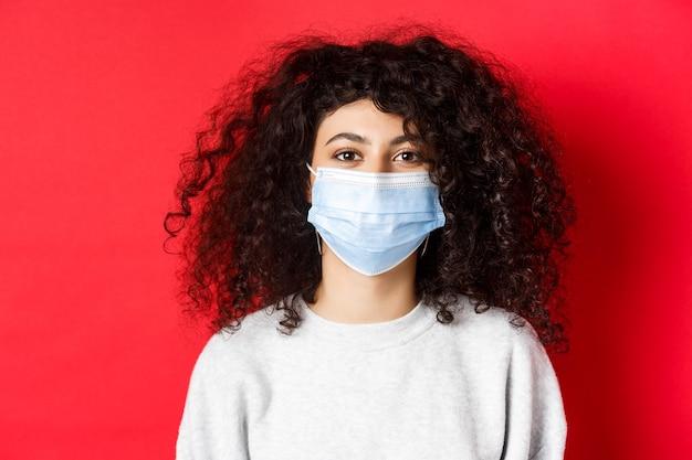 Covid-19 y concepto de pandemia. primer plano de mujer joven moderna con cabello rizado, con máscara médica de coronavirus, sonriendo a la cámara, fondo rojo.