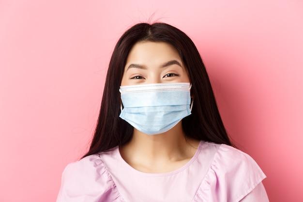 Covid-19 y concepto de personas sanas. primer plano de la alegre muchacha adolescente asiática con máscara médica y sonriendo con los ojos, de pie contra el fondo de color rosa.