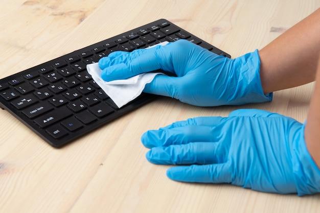 Covid-19 desinfección del espacio de oficina limpiando el virus corona limpieza y desinfección de su espacio de trabajo. toallitas desinfectantes para limpiar la superficie del escritorio, teclado, mouse.