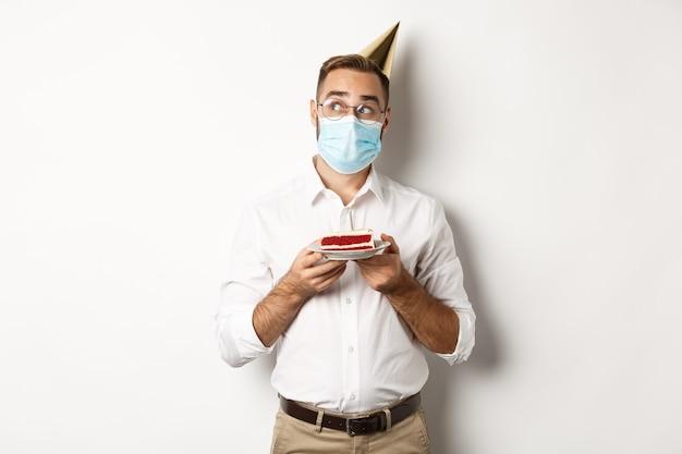 Covid-19, distanciamiento social y celebración. hombre pensativo sosteniendo pastel de cumpleaños, pidiendo deseos y usando mascarilla en cuarentena, fondo blanco.