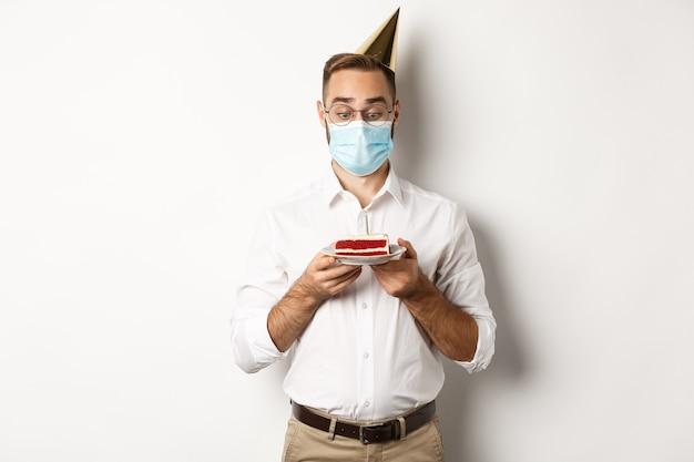 Covid-19, distanciamiento social y celebración. hombre que mira emocionado el pastel de cumpleaños, con máscara médica de la pandemia de coronavirus, fondo blanco.