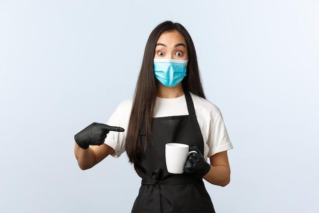 Covid-19, distanciamiento social, pequeño negocio de cafetería y prevención del concepto de virus. emocionado barista asiático, empleada de café femenino en máscara médica y guantes apuntando a la taza con café