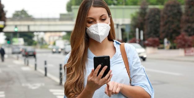 Covid-19 mujer joven con máscara ffp2 usando un teléfono inteligente en la calle de la ciudad