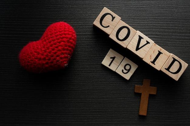 Covid-19 nombre del virus corona de la palabra de texto de wuhan sobre fondo de madera drak con amor de corazón.