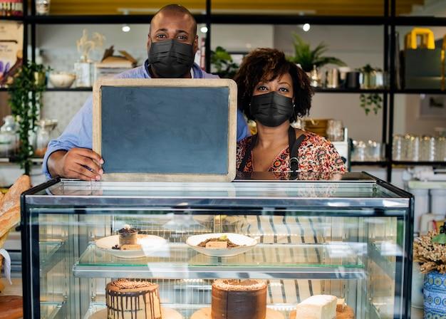 Covid 19, pareja reapertura de negocios nuevo letrero de pizarra normal