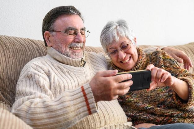 Covid-19 quédate en casa. feliz pareja de jubilados, haciendo una videollamada familiar con teléfono móvil. distanciamiento social, expresión positiva.