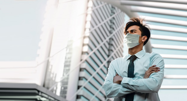 Covid-19 situación en concepto de negocio. empresario con máscara quirúrgica de pie en la ciudad