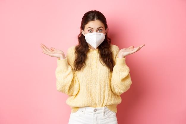 Covid lockdown y concepto pandémico mujer joven despistada en respirador médico no sé nada encogiéndose de hombros con cara confundida no tiene idea de estar parado sobre una pared rosa