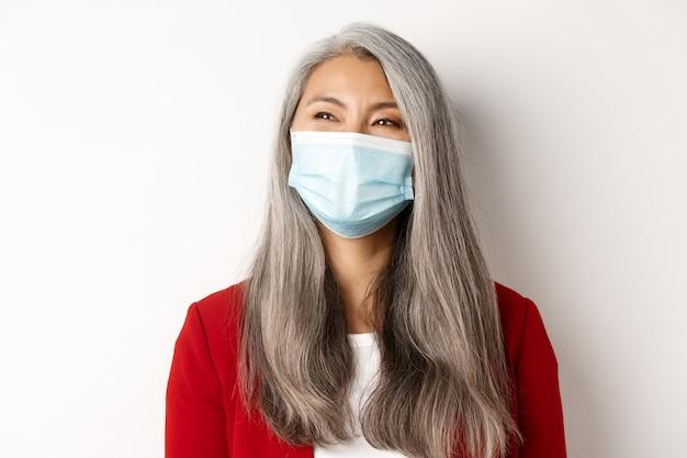 Covid, pandemia y concepto empresarial. cerca de feliz empresaria asiática con cabello gris, con máscara médica y sonriendo, mirando a la izquierda con cara alegre, fondo blanco.