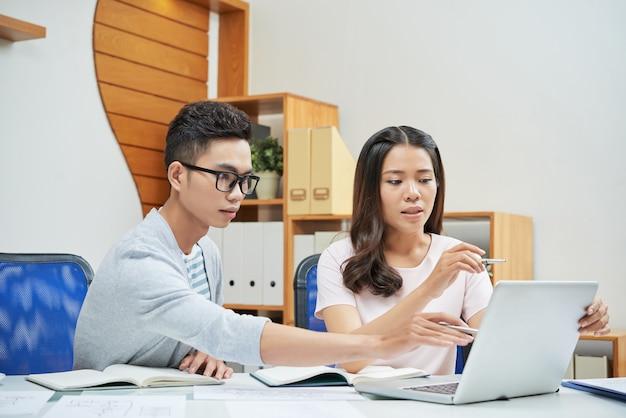 Coworking jóvenes empresarios usando laptop