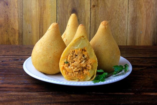 Coxinha en el plato, cocina tradicional brasileña, bocadillos rellenos de pollo.