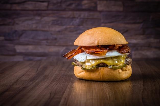 Craft burger de carne con queso, huevo, tocino y pepinillos en mesa de madera