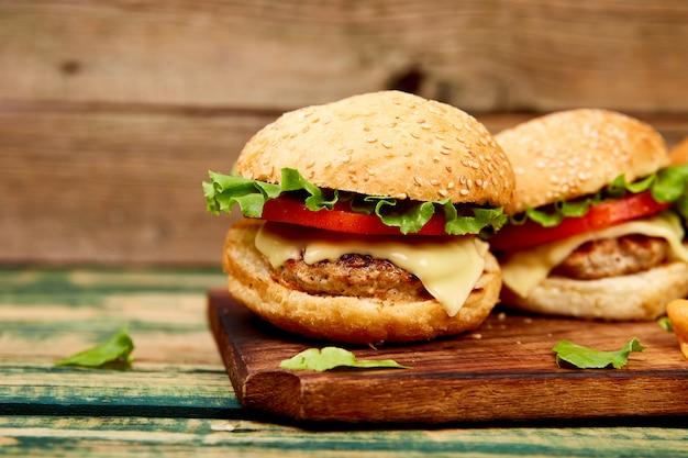 Craft hamburguesa de carne en la mesa de madera aislada sobre fondo negro.