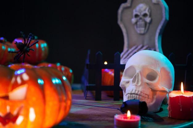 Cráneo aterrador bajo la luz de las velas en una mesa de madera para la celebración de halloween. calabaza espeluznante.