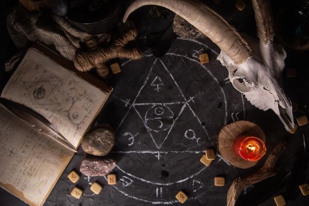 Cráneo de cabra blanca con cuernos, libro antiguo abierto con hechizos mágicos, runas, velas y hierbas en la mesa de brujas, endecha plana