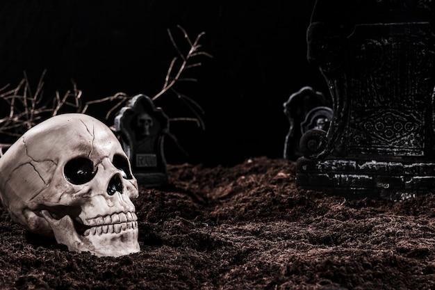 Cráneo en el cementerio nocturno con lápidas