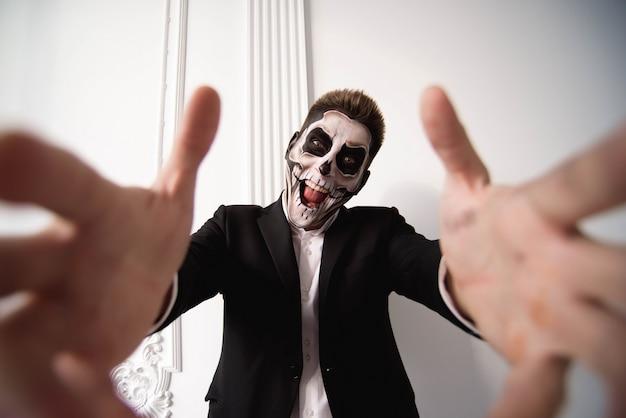 Cráneo conforman retrato de hombre joven. arte de cara de halloween