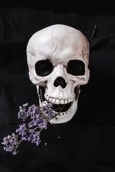 Cráneo espeluznante con flores secas