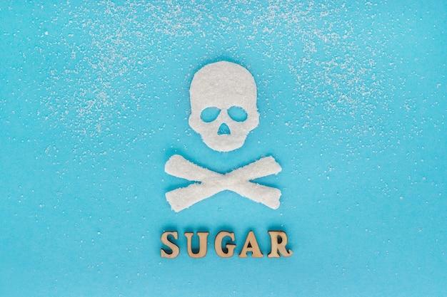 Cráneo huesos azúcar, esparcimiento de azúcar granulada, texto azúcar