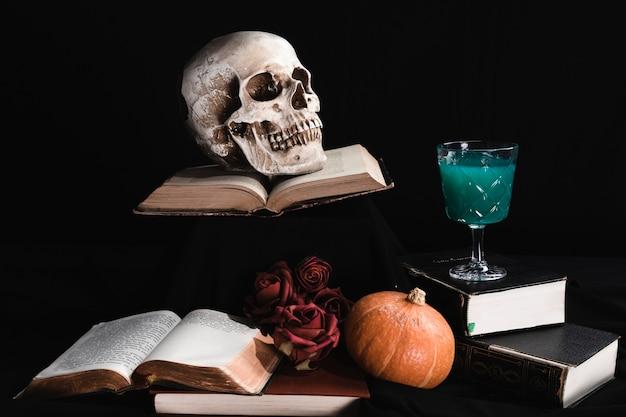 Cráneo humano con bebida verde y libros