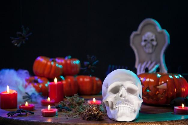 Cráneo humano espeluznante con calabaza aterradora detrás en la mesa de madera para la celebración de halloween. celebración de halloween.