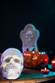 Cráneo humano espeluznante con otras decoraciones de halloween en una mesa de madera. celebración de halloween.