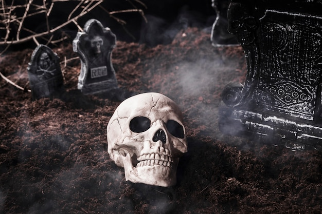 Cráneo humano en humo en el cementerio de halloween