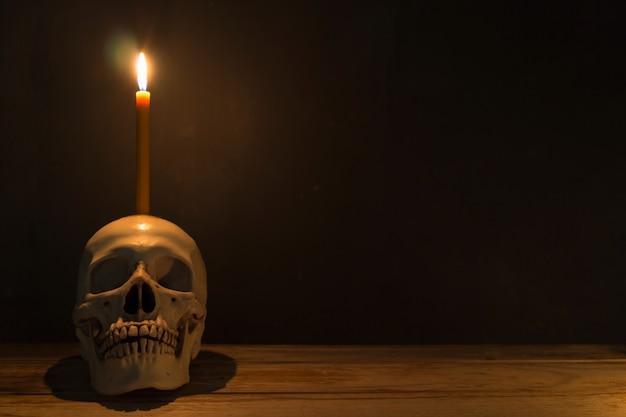 Cráneo humano con luz de vela en mesa de madera en el fondo oscuro